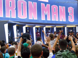 The Marvel booth decked out with all the Iron Man suits as attendees vie for some giveaways.
